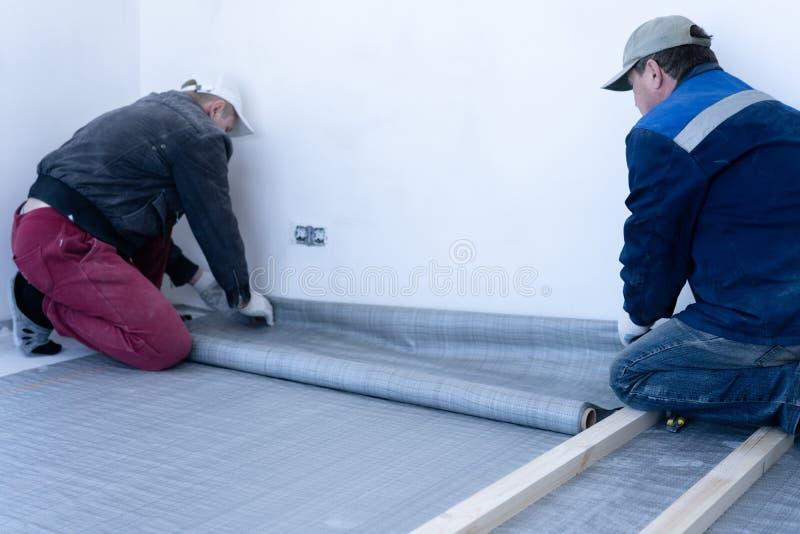 熟练木匠登上松木地板-环境友好的地板 胶合在滞后下的绝缘材料层数在 免版税图库摄影