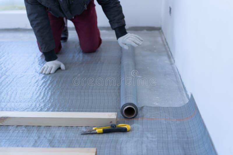 熟练木匠登上松木地板-环境友好的地板 胶合在滞后下的绝缘材料层数在 库存照片
