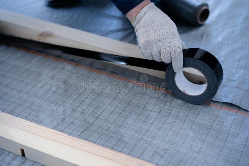 熟练木匠登上松木地板-环境友好的地板 胶合在滞后下的绝缘材料层数在 免版税库存图片