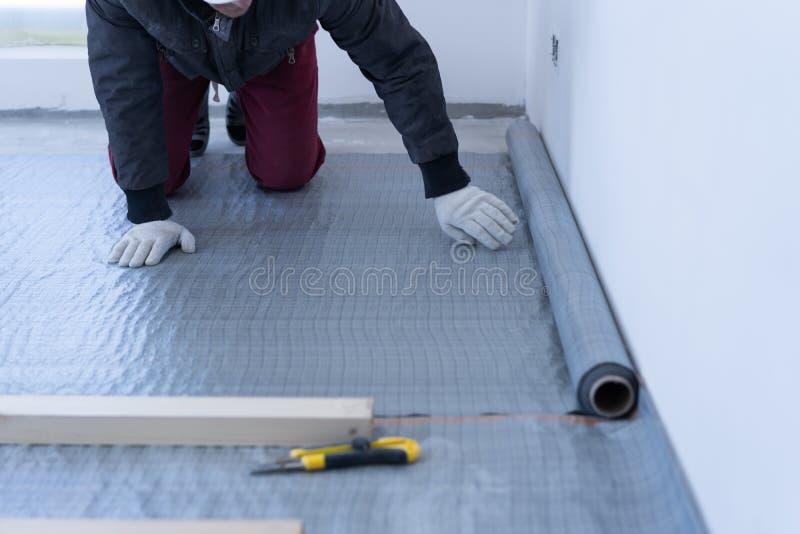 熟练木匠登上松木地板-环境友好的地板 胶合在滞后下的绝缘材料层数在 图库摄影