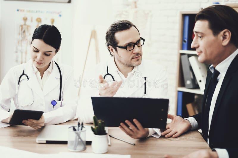 熟练的医生在医疗办公室劝告商人 与主治医师的咨询 免版税库存照片