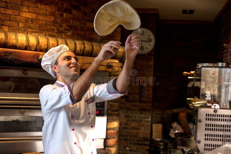 熟练的厨师面团为薄饼辗压做准备用手和Th 库存图片