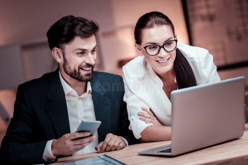 熟练的可靠伙伴坐和与膝上型计算机一起使用 库存照片
