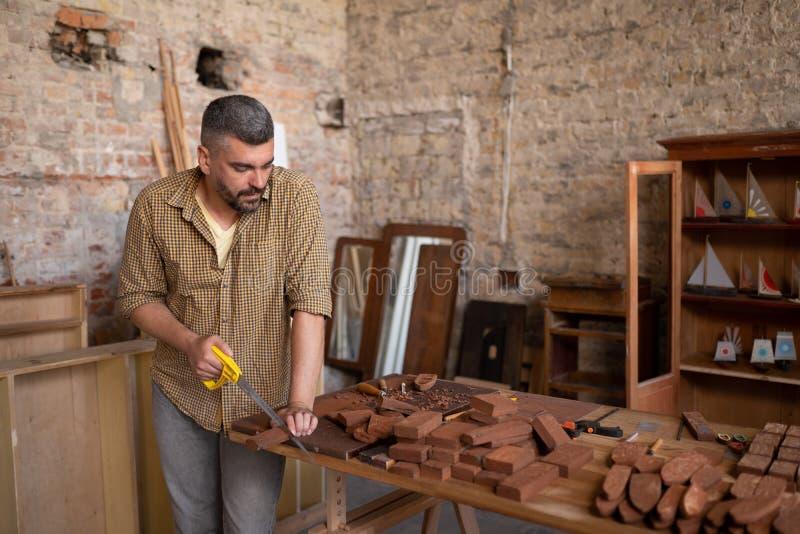 熟练的木匠切开一块木头 免版税图库摄影