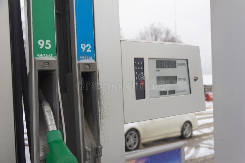 燃料分与的枪和汽油品牌的名字在俄国AI 95和AI 92的和一个信息面板用有词的俄语 免版税图库摄影