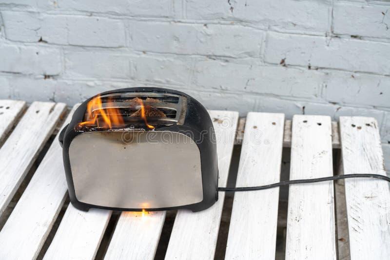 燃烧的多士炉 有多士风行在白色背景的火两个切片的多士炉 库存图片