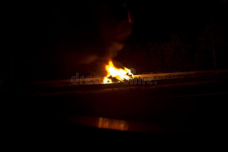 燃烧的汽车是火焰 消防队员熄灭火 对汽车的集合火 图库摄影