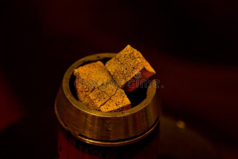 燃烧的立方体煤炭在黑暗的背景的一个金属水烟筒碗特写镜头闷燃 炭烬宏观顶视图拷贝空间 图库摄影