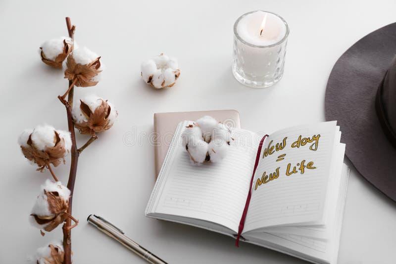 燃烧的蜡烛、棉花花和开放笔记本与文本新的天新的生活在白色背景 免版税库存照片