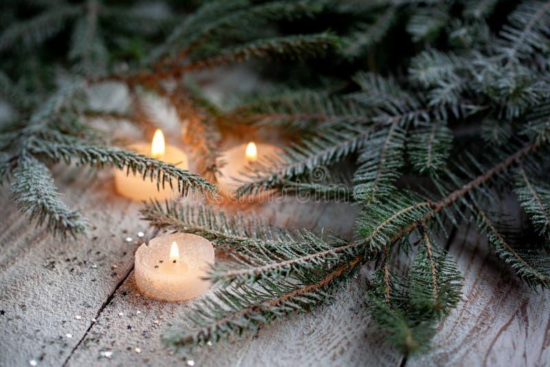 燃烧的蜡烛和圣诞装饰在雪与杉木分支在白色木背景 免版税库存照片