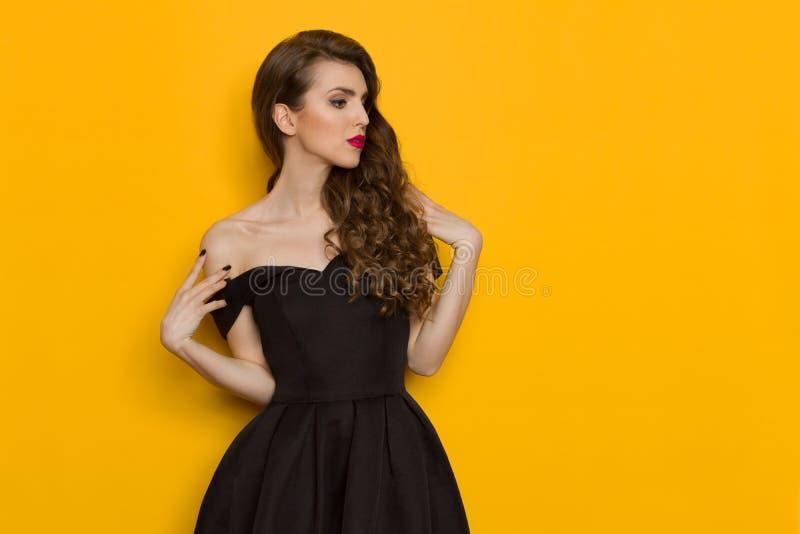 黑燕尾服的美丽的典雅的少妇 免版税库存图片
