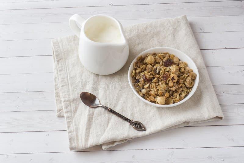 燕麦剥落、粒子和坚果干早餐  在一块板材和一个牛奶罐的Muesli用酸奶 库存照片