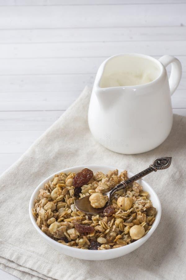 燕麦剥落、粒子和坚果干早餐  在一块板材和一个牛奶罐的Muesli用酸奶 免版税库存图片