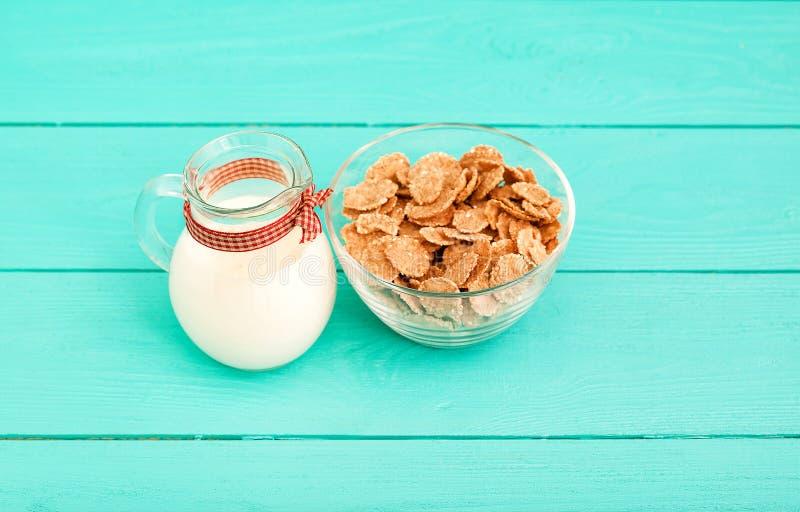 燕麦剥落和水罐在蓝色木厨房的牛奶 顶视图和拷贝空间 嘲笑 早餐 库存照片