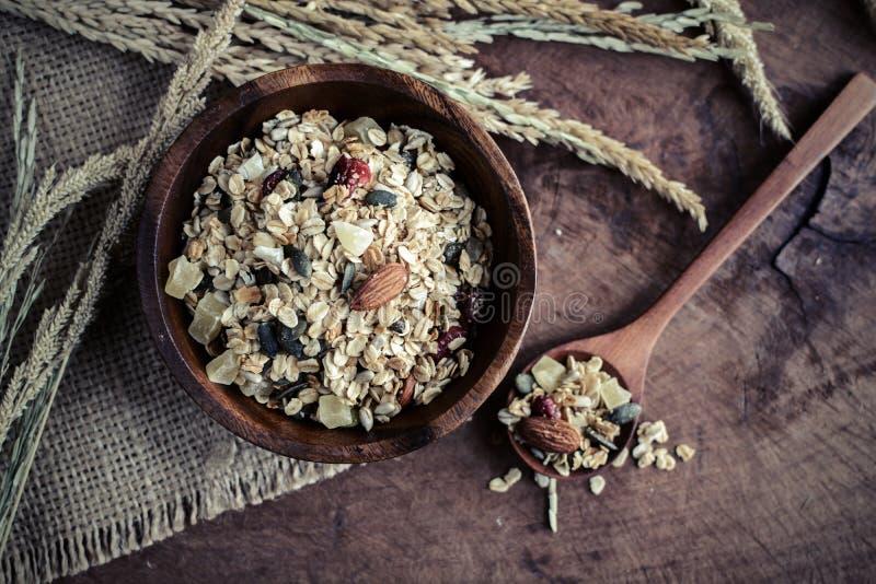 燕麦和全麦五谷在木桌上的木碗剥落 库存图片