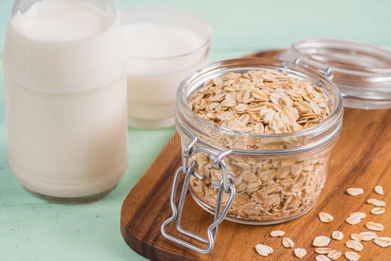 燕麦在玻璃瓶子和牛奶瓶剥落 免版税库存照片