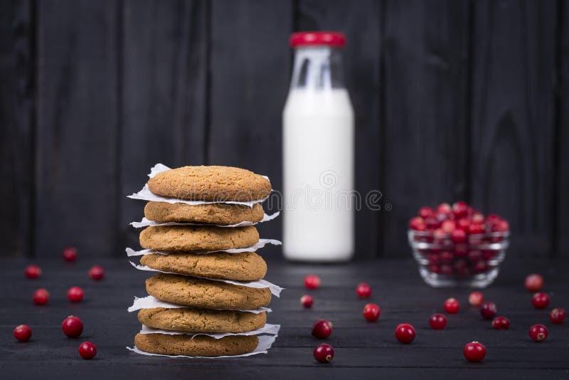 燕麦曲奇饼、牛奶和未加工的蔓越桔在黑木背景,关闭 免版税库存照片