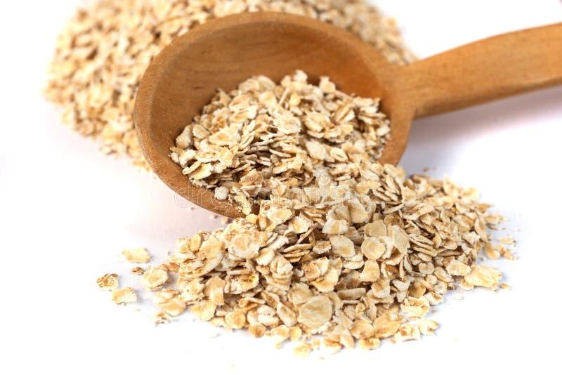 燕麦片堆与木匙子的在白色 免版税库存照片