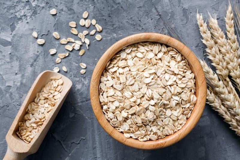 燕麦片或燕麦在石背景的木碗剥落 免版税库存照片