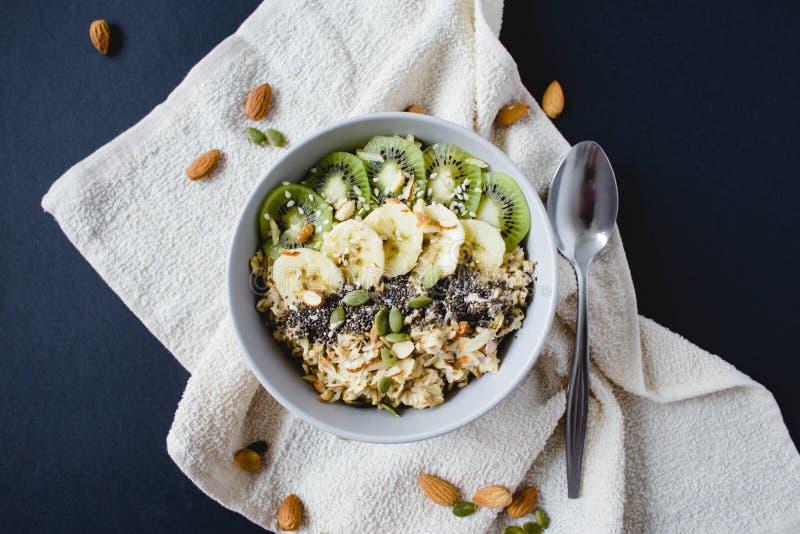 燕麦粥健康早餐用香蕉、猕猴桃在一块白色餐巾和杏仁 图库摄影