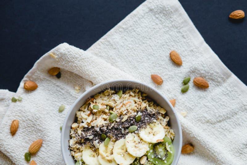 燕麦粥健康素食主义者早餐用在一个白色餐巾和杏仁的果子 库存图片
