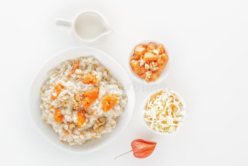燕麦粥用南瓜和坚果、沙拉、苹果和水罐在白色背景的牛奶 在视图之上 免版税图库摄影