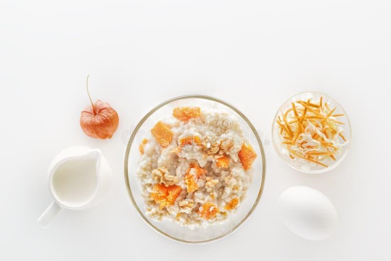 燕麦粥用南瓜和坚果、沙拉、苹果和水罐在白色背景的牛奶 库存图片