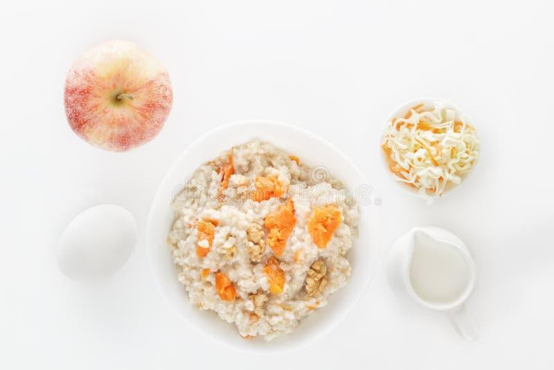 燕麦粥用南瓜和坚果、沙拉、鸡蛋和一个水罐在白色背景的牛奶 在视图之上 免版税库存照片