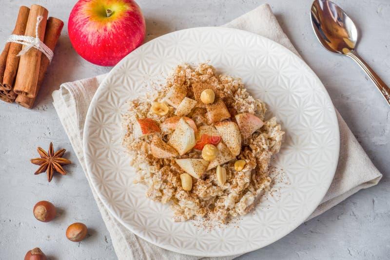 燕麦粥用新鲜的苹果、坚果和桂香早餐在Th 图库摄影