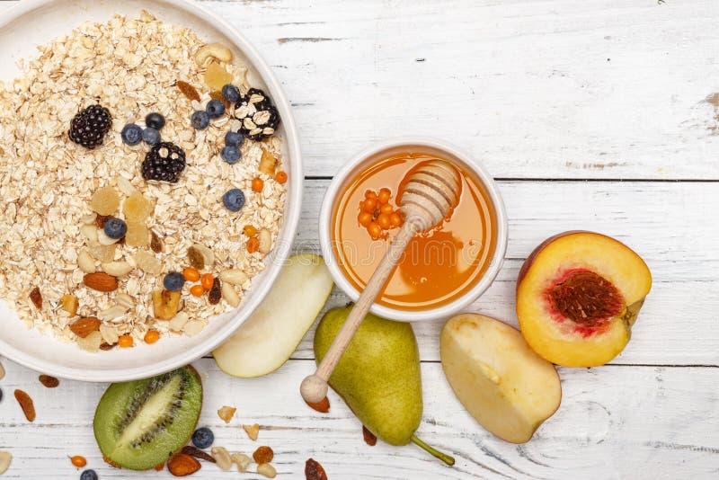 燕麦粥用果子和蜂蜜在一张白色木桌上 健康的食物 顶视图 免版税图库摄影