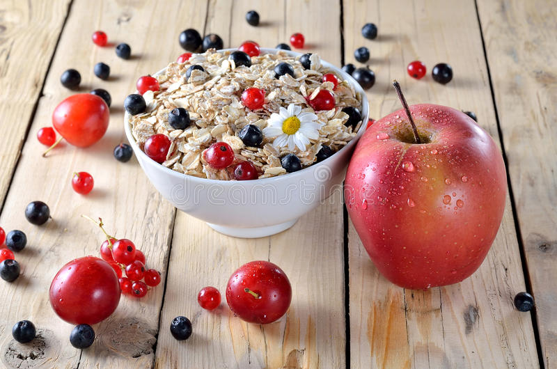 燕麦粥用莓果和新鲜的苹果在一张木桌上 库存图片