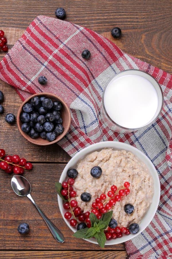 燕麦粥用莓果和牛奶在一个碗在一张棕色木桌上 早餐健康食物 图库摄影