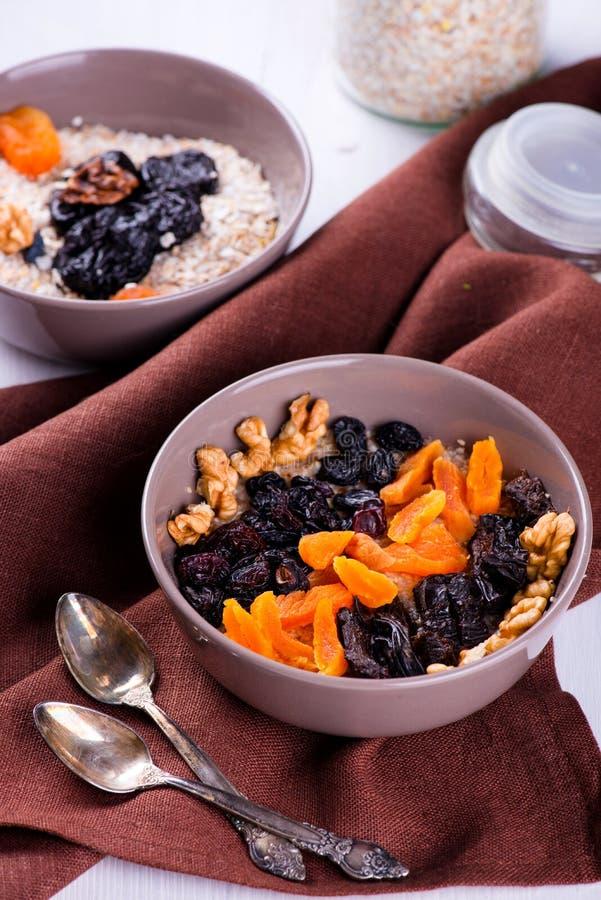 燕麦粥用葡萄干,杏干,在碗的李子 库存图片