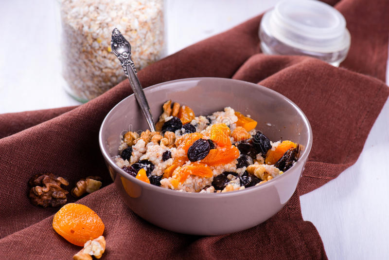 燕麦粥用葡萄干,杏干,在碗的李子 库存照片