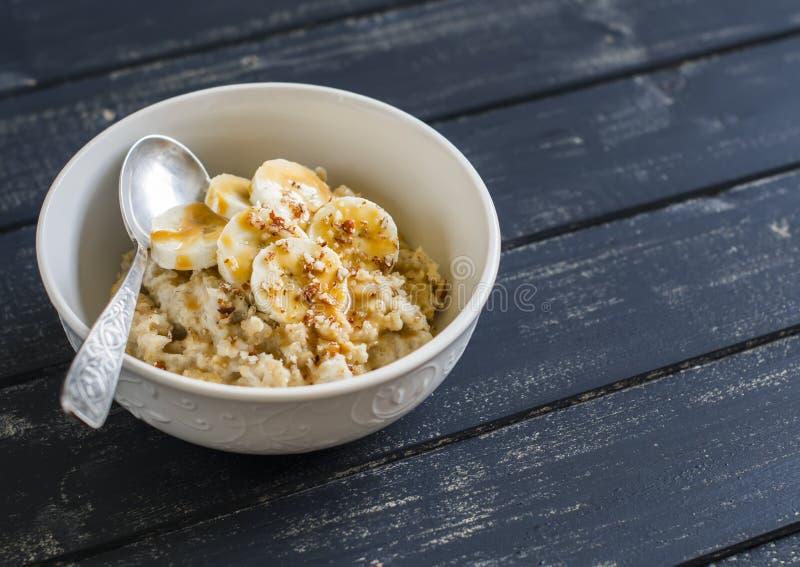 燕麦粥用香蕉、焦糖调味汁和山核桃果在一个白色碗黑暗的木表面上 库存图片