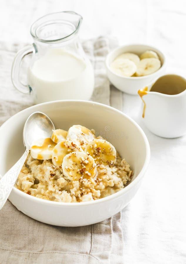 燕麦粥用香蕉、焦糖调味汁和山核桃果在一个白色碗轻的表面上 图库摄影