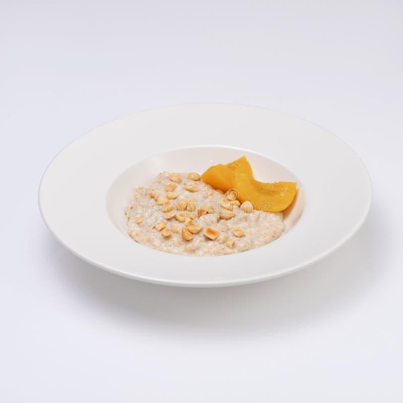 燕麦粥粥板材与坚果和桃子的 每天热和健康早餐,饮食食物 背景查出的白色 库存照片