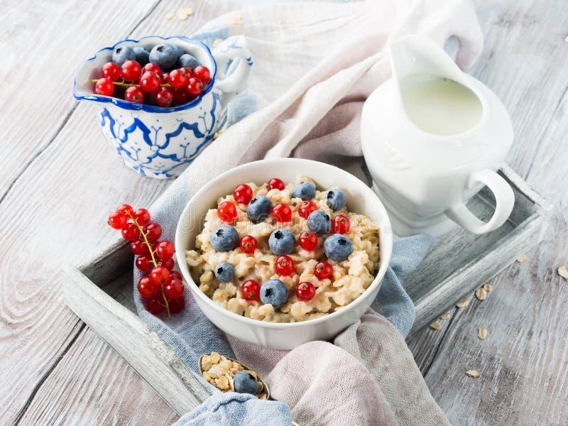 燕麦粥粥用在一个木盘子的蓝莓 免版税库存图片