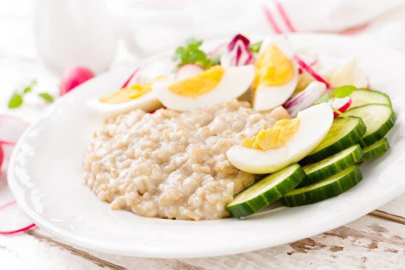 燕麦粥粥用熟蛋和菜沙拉用新鲜的萝卜、黄瓜和莴苣 早餐饮食健康 免版税库存图片