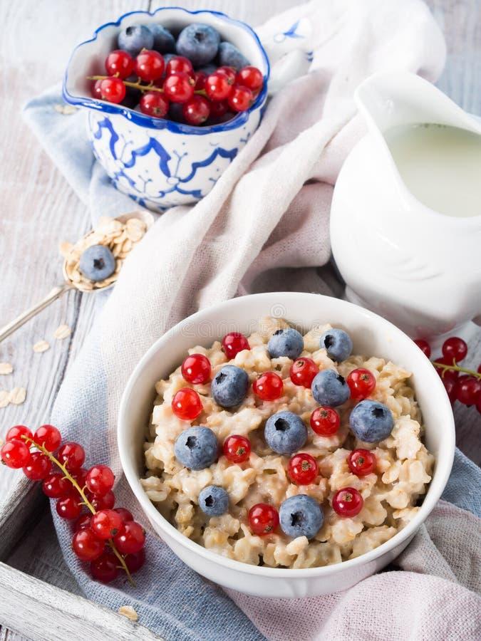 燕麦粥粥用蓝莓和在土气的红浆果求爱 库存照片