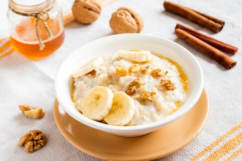 燕麦粥粥用香蕉、坚果和蜂蜜 免版税库存照片