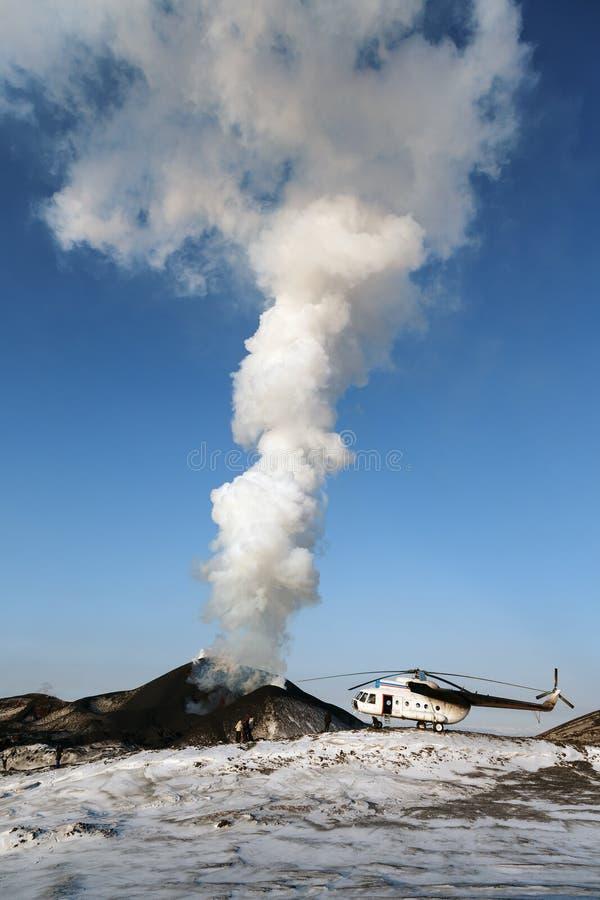 爆发在堪察加、直升机和游人近的抽烟的火山的扎尔巴奇克火山火山 免版税库存照片