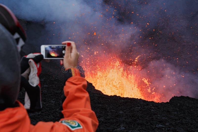 爆发在堪察加,女孩的扎尔巴奇克火山火山拍摄了火山口火山的熔岩湖在手机 免版税图库摄影