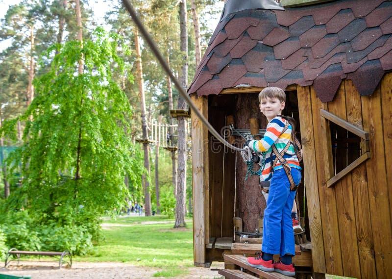 爬上入树上小屋的男孩 室外健康的比赛 库存照片