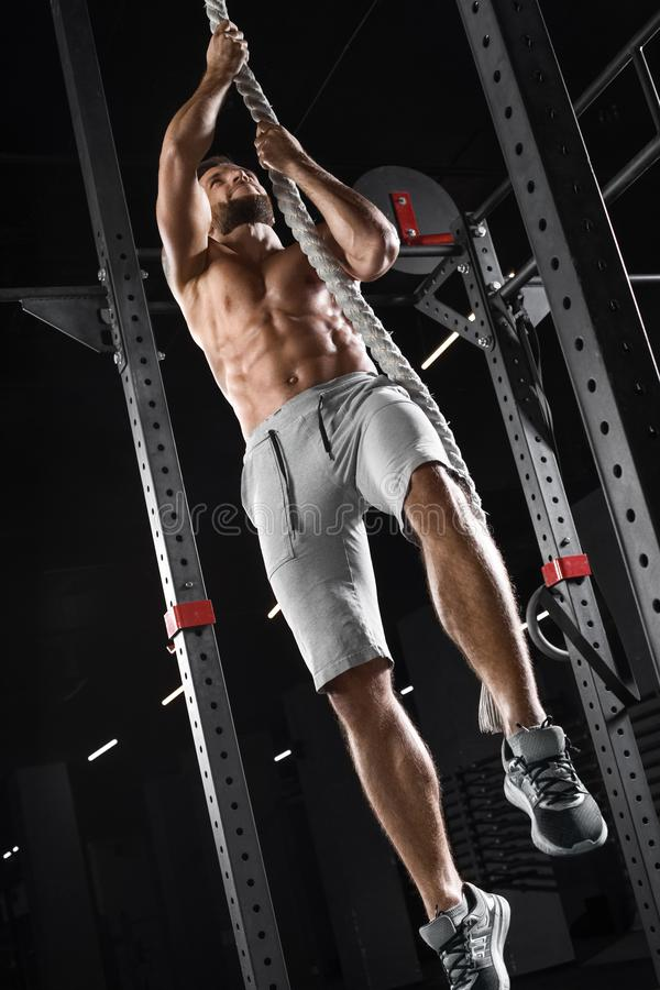 爬上在健身房的Crossfit运动员绳索 做锻炼,赤裸躯干吸收的肌肉人 库存照片