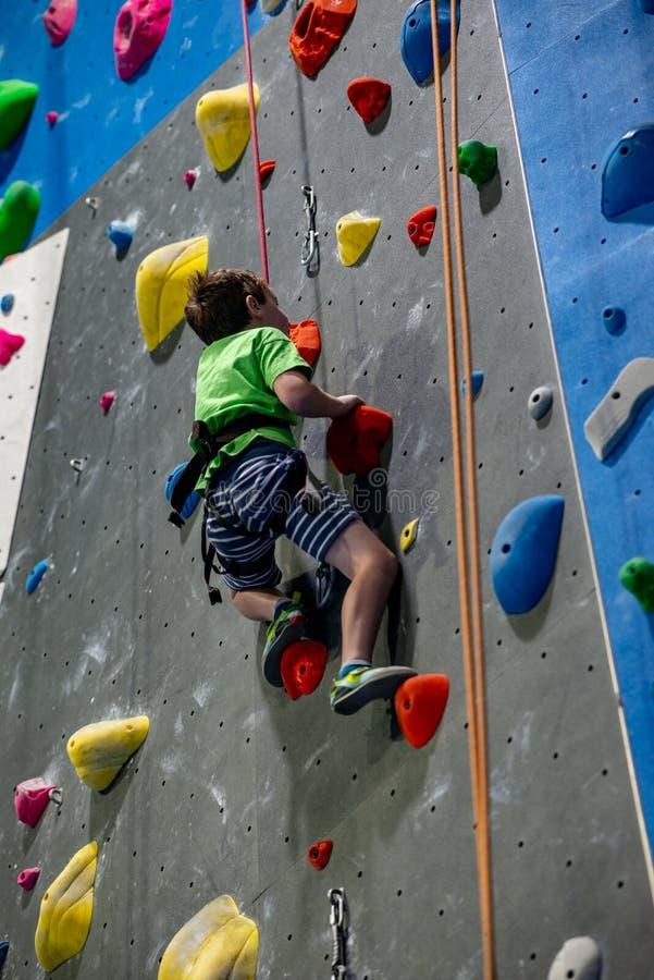 爬上在室内岩石健身房的实践墙壁上的年轻男孩 免版税库存图片