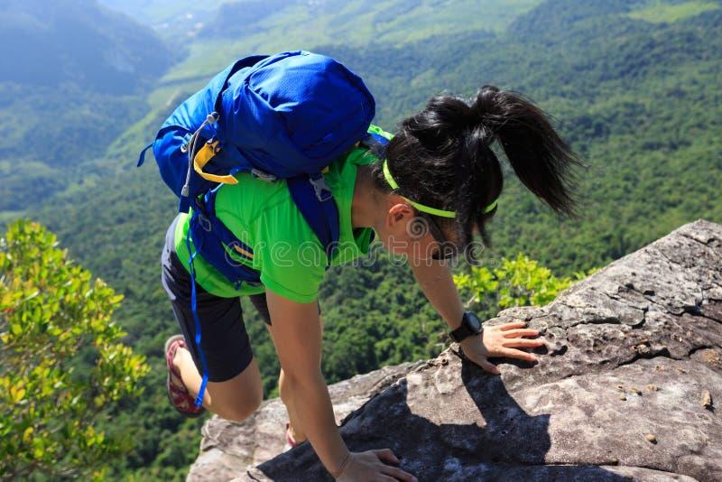 爬上在山岩石的妇女背包徒步旅行者 免版税库存图片