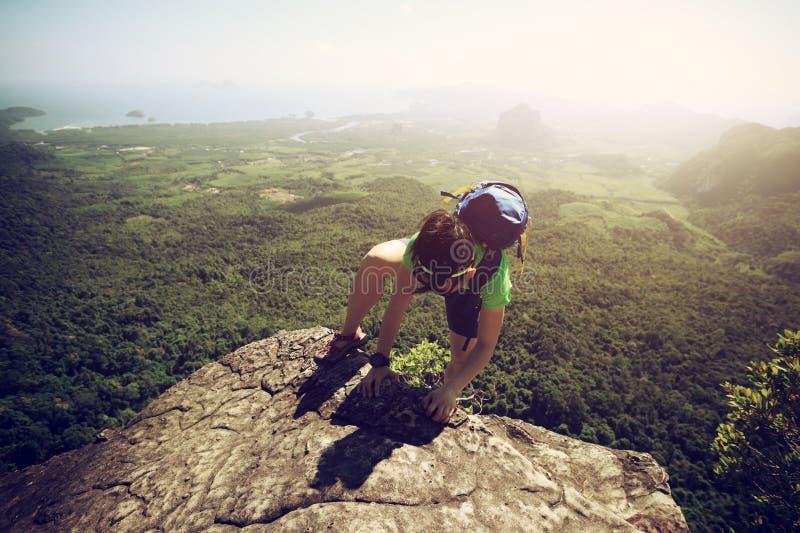 爬上在山岩石的妇女背包徒步旅行者 库存图片
