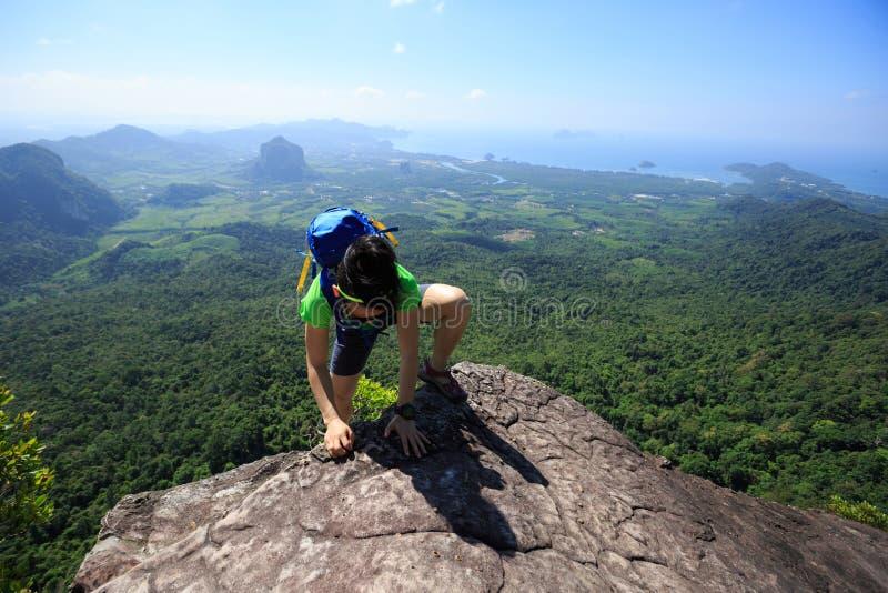 爬上在海边山岩石的背包徒步旅行者 免版税库存照片