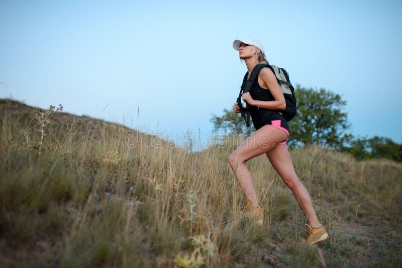 爬上年轻美好的白种人妇女行家女孩的远足喂 图库摄影